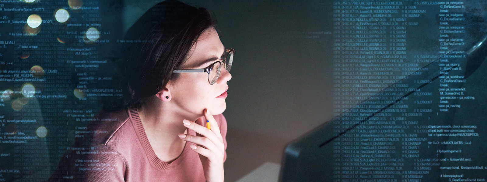 Woman with left hand on chin looking at data on computer screen